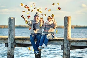 people sitting on a dock throwing leaves